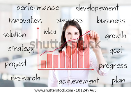 Young business woman writing growth graph with business related text. Office background. - stock photo