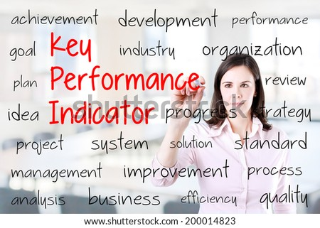 Young business woman writing key performance indicator (kpi) concept. Office background.  - stock photo