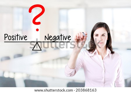 Young business woman writing positive and negative compare on balance bar. Office background. - stock photo