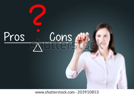 Young business woman writing pros and cons compare on balance bar. Blue background. - stock photo