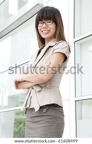 Young Business Women arms crossed standing in front building block - stock photo