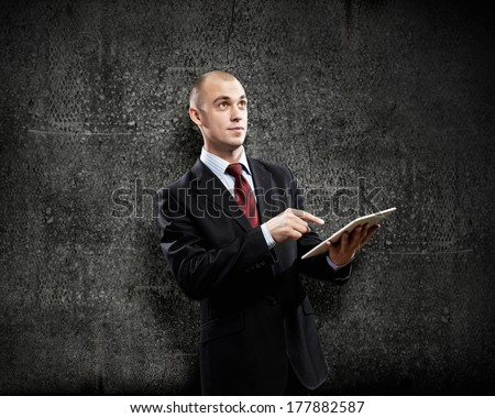 Young businessman against grey background using tablet pc - stock photo