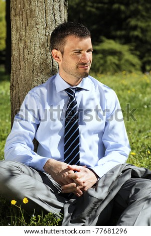 young businessman alone in nature in summer - stock photo