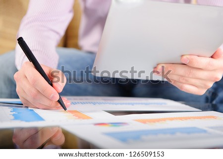 Young businessman analyzing charts. Low angle view. - stock photo