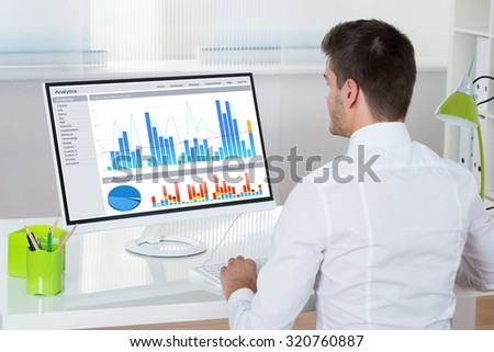 Young Businessman Analyzing Graphs On Desktop Computer In Office - stock photo