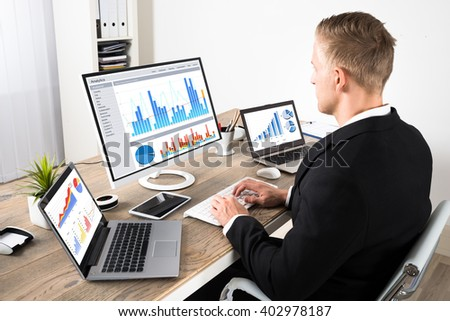 Young Businessman Analyzing On Graphs On Computer With Digital Tablet And Laptop In Office - stock photo
