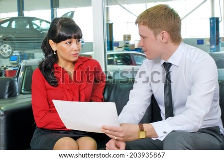 Young businessman and business lady communicate in the negotiations room of automobile shop (car repair shop) - stock photo