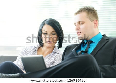Young businessman and business woman sitting at office lobby on leather sofa working with tablet pc - stock photo