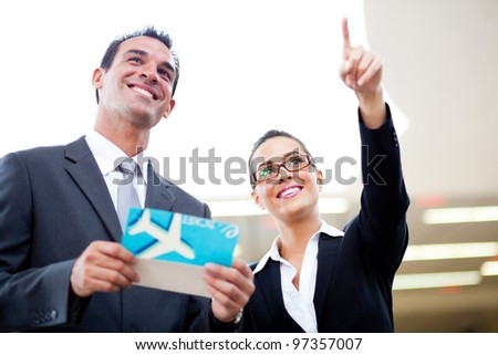 young businessman and businesswoman looking at boarding information at airport - stock photo
