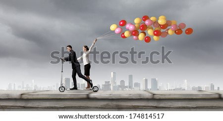 Young businessman and businesswoman riding scooter on roof of building - stock photo