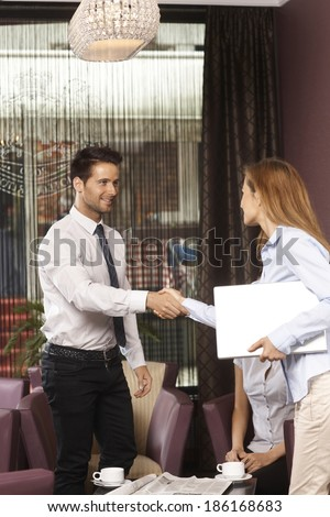 Young businessman and businesswoman shaking hands at coffee bar. - stock photo