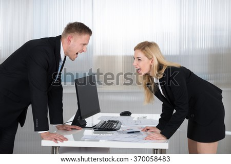 Young businessman and businesswoman shouting at each other at desk in office - stock photo
