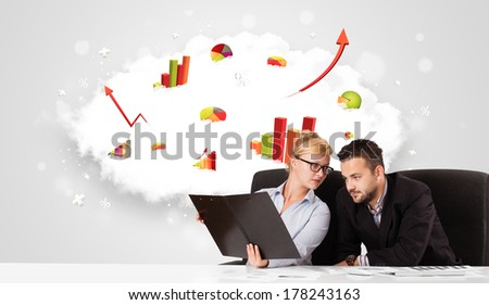 Young businessman and businesswoman with cloud in the background containing colorful graphs and diagrams - stock photo