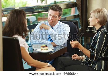 Young businessman and businesswomenhaving a meeting in cafe. - stock photo
