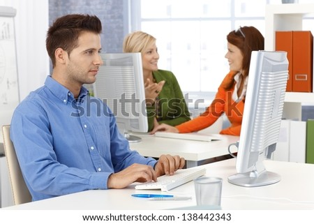 Young businessman and colleagues working in office, sitting at desk, using desktop computer. - stock photo