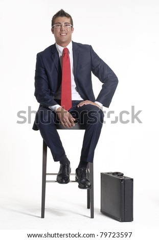 Young businessman and his suitcase sitting on a chair  on white background. - stock photo