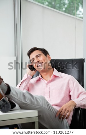 Young businessman answering phone call at office with his legs on the desk - stock photo