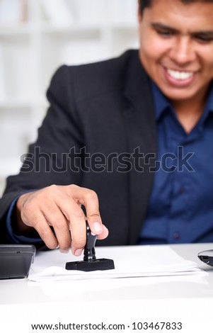 Young businessman at his desk stamping document - stock photo