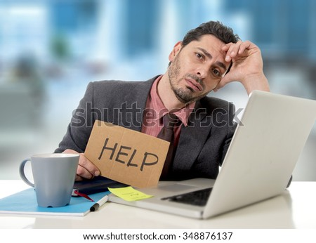 young businessman at office desk working on computer laptop asking for help holding cardboard sign looking desperate and depressed in business stress overwhelmed and overwork concept - stock photo