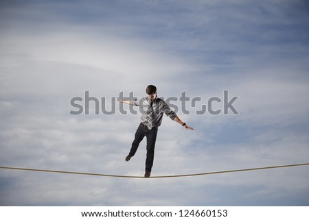 Young businessman balancing on a rope in the sky. - stock photo