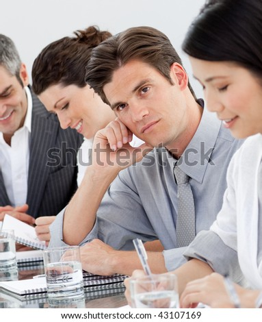 Young businessman bored at a presentation with his colleagues - stock photo