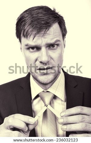Young businessman breaking a cigarette- concept for give up smoking - stock photo