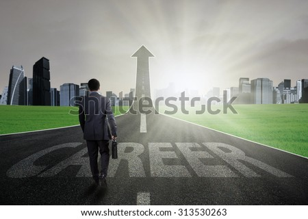 Young businessman carry a briefcase and walk on the path with a career text going up as an arrow - stock photo