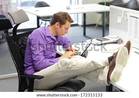 Young businessman caucasian in his office  working with tablet - bad sitting posture  - stock photo