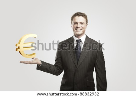 Young  businessman chooses a Gold Euro Sign.On a gray background - stock photo