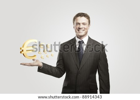 Young  businessman chooses a Gold Euro Signs.On a gray background - stock photo