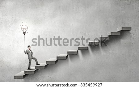 Young businessman climbs ladder of success with lightbulb balloon in hand - stock photo