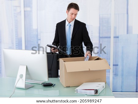 Young businessman collecting office supply in cardboard box at office desk - stock photo