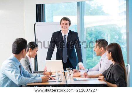 Young businessman conducting meeting with his colleagues - stock photo