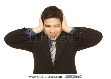 Young businessman covering his ears - stock photo