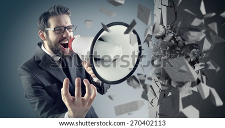 Young businessman crushing concrete wall with a megaphone - stock photo