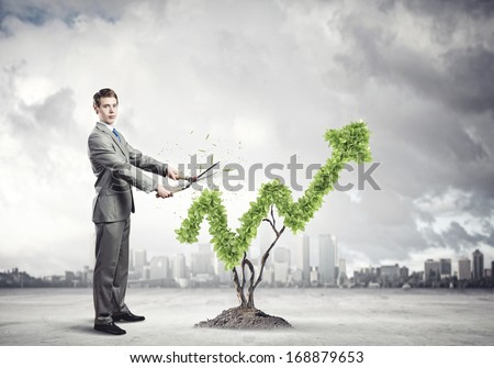 Young businessman cutting bush in shape of graph - stock photo