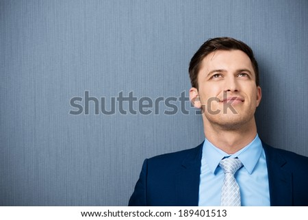 Young businessman deep in thought standing leaning against a clean blackboard staring up into the air as he tries to come up with a solution to a problem, with copyspace - stock photo