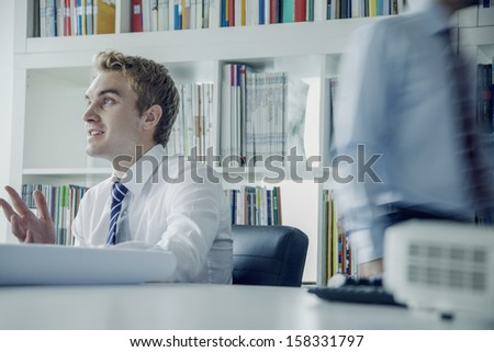 Young businessman discussing at a business meeting with colleague behind him - stock photo