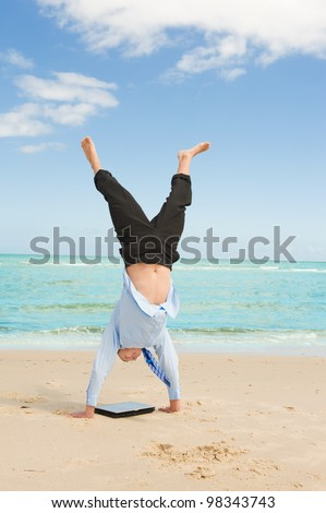 young businessman doing handstand on the beach after a big deal - stock photo