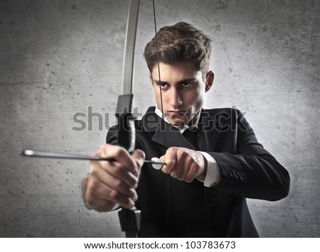 Young businessman drawing a bow - stock photo