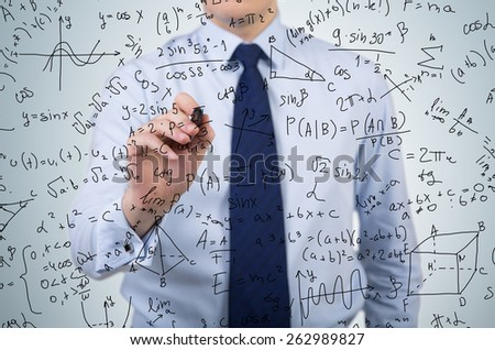 young businessman drawing mathematics equations and formulas - stock photo