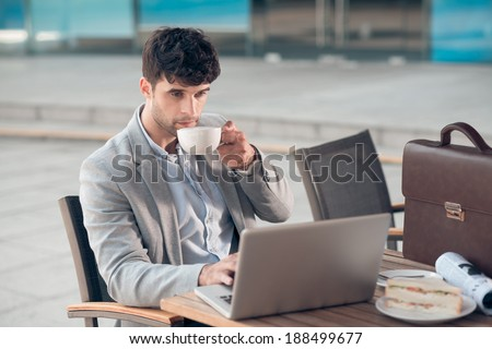 Young businessman drinking coffee and working on laptop in a cafe - stock photo
