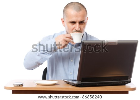Young businessman drinking coffee while reading something on his laptop - stock photo