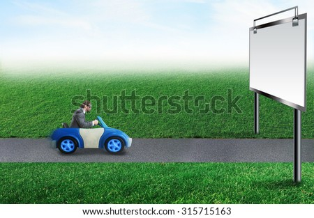 Young businessman driving a toy car - stock photo