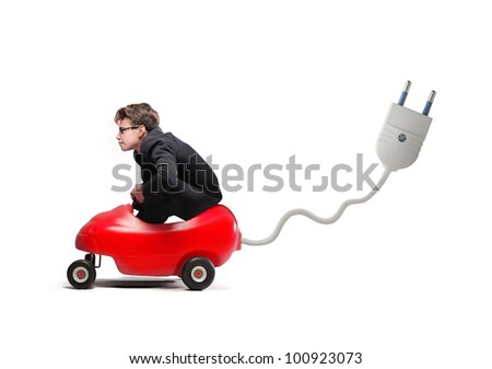 Young businessman driving an electric toy car - stock photo