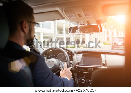 Young businessman driving to work, view over the shoulder - stock photo