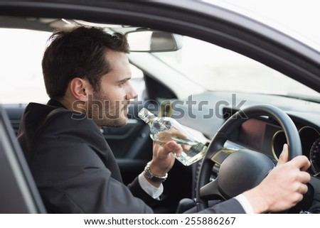 Young businessman driving while drunk in his car - stock photo