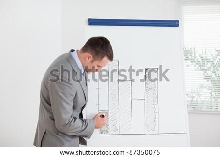 Young businessman editing column graph - stock photo
