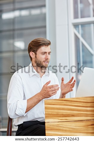 Young businessman engaged in a conversation on his laptop in a corporate setting - stock photo