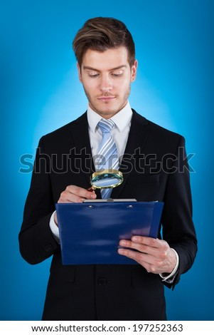 Young businessman examining document on clipboard against blue background - stock photo